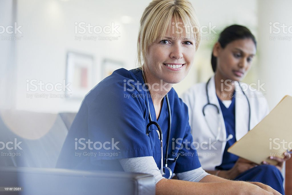 Portrait of smiling nurse sitting with doctor in hospital stock photo