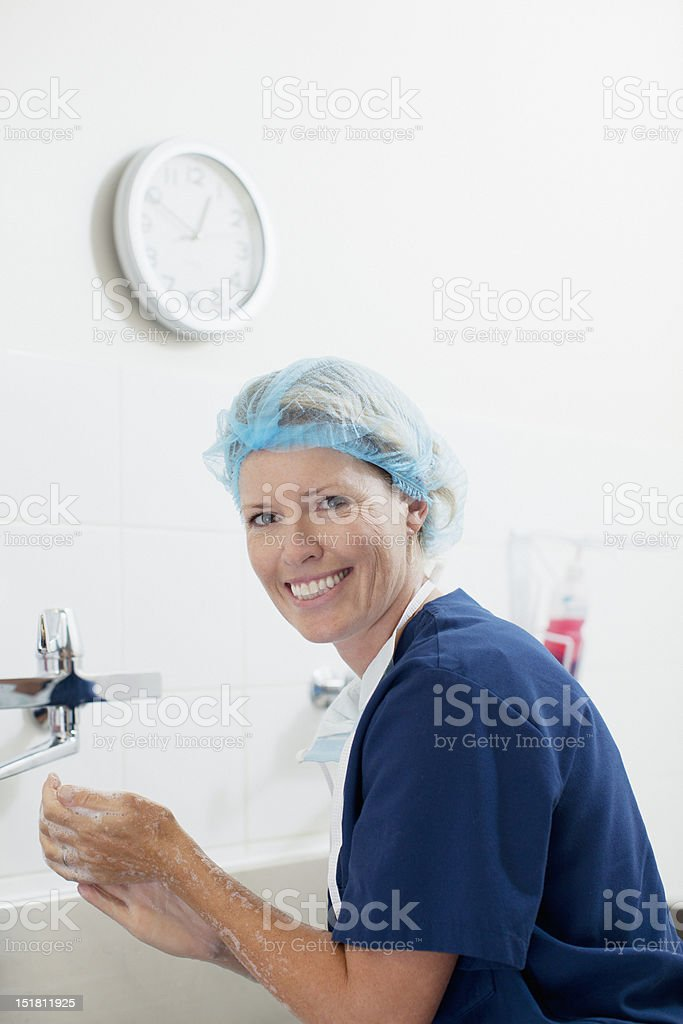 Portrait of smiling nurse washing hands royalty-free stock photo