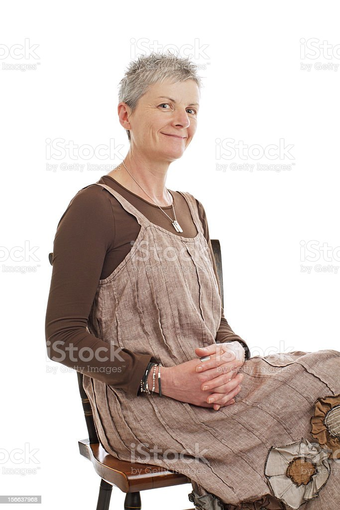 Portrait of smiling older woman sitting sideways stock photo