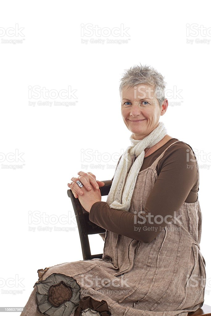 Portrait of smiling older woman sitting sideways royalty-free stock photo