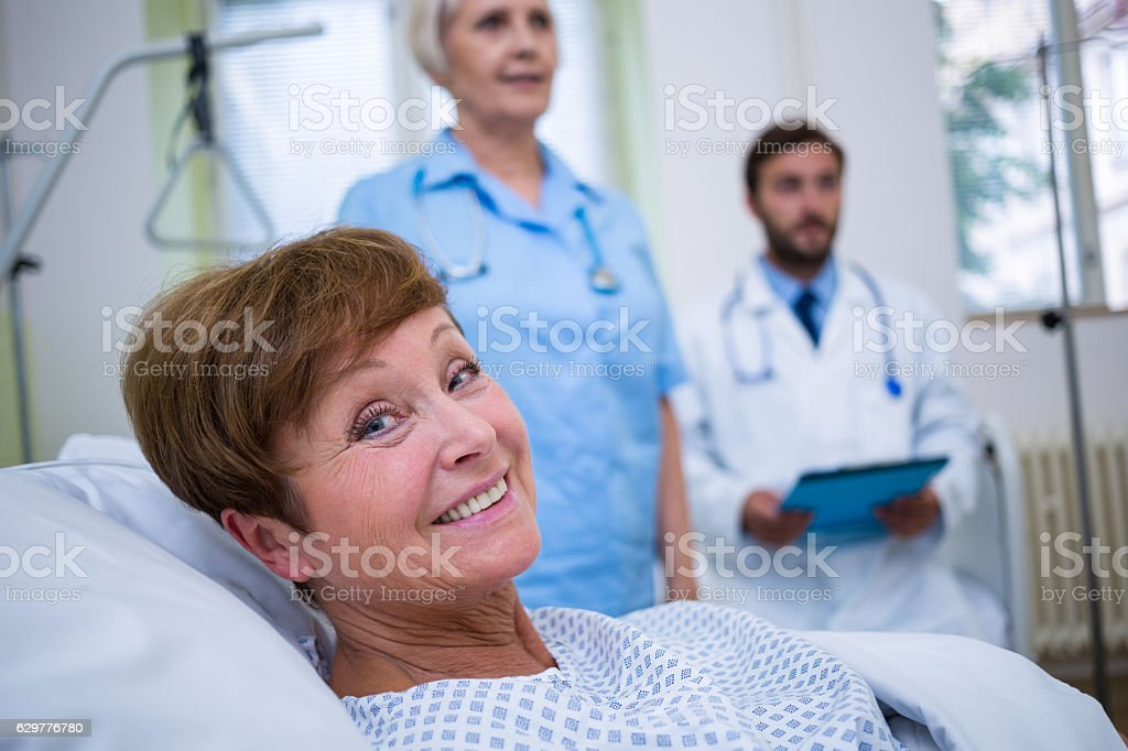 Portrait of smiling patient lying on bed stock photo