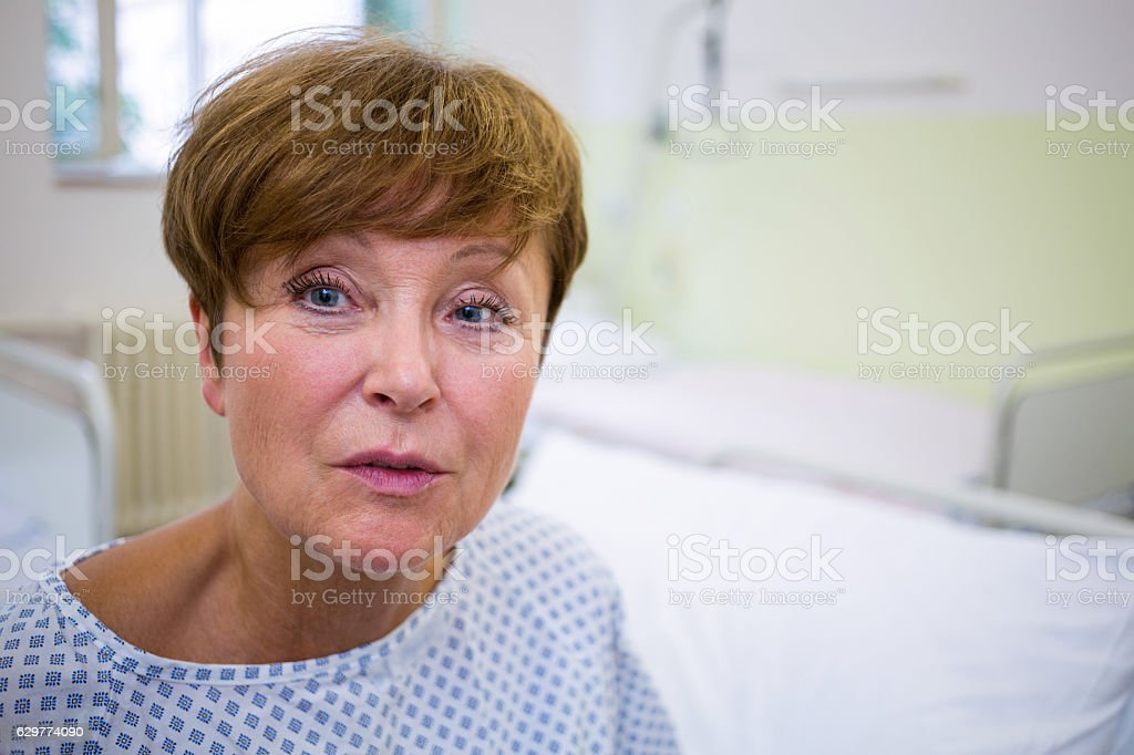 Portrait of smiling patient sitting on bed stock photo