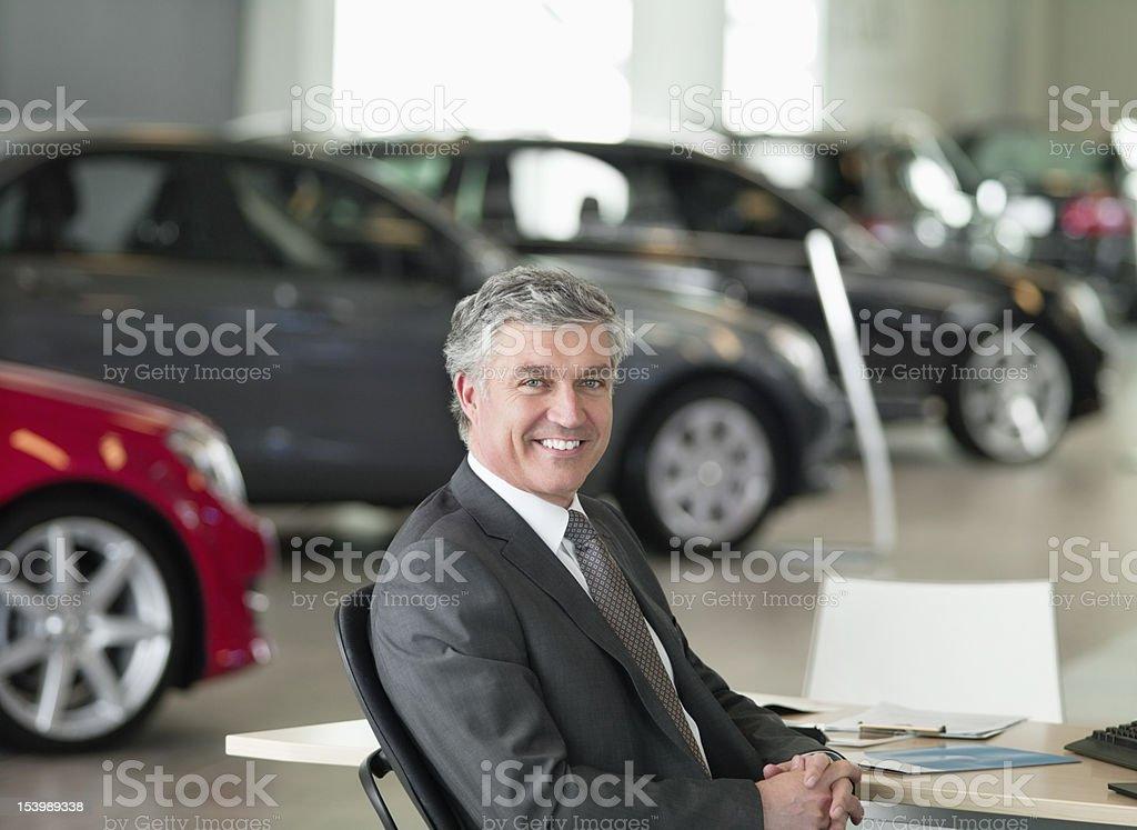 Portrait of smiling salesman sitting at desk in car dealership showroom royalty-free stock photo