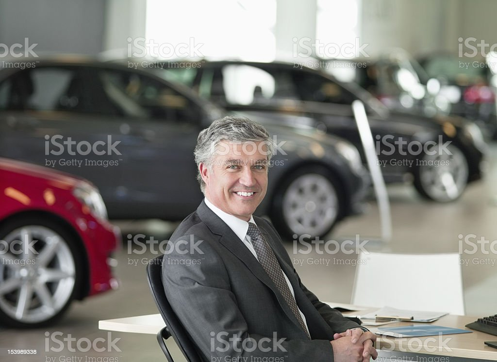 Portrait of smiling salesman sitting at desk in car dealership showroom stock photo