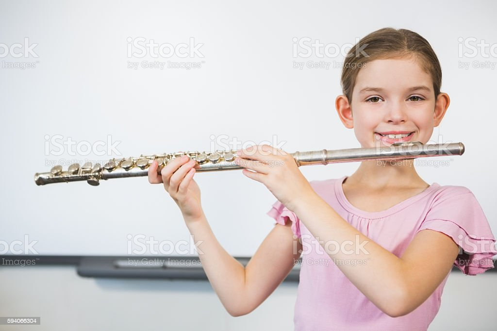 Portrait of smiling schoolgirl playing flute in classroom stock photo