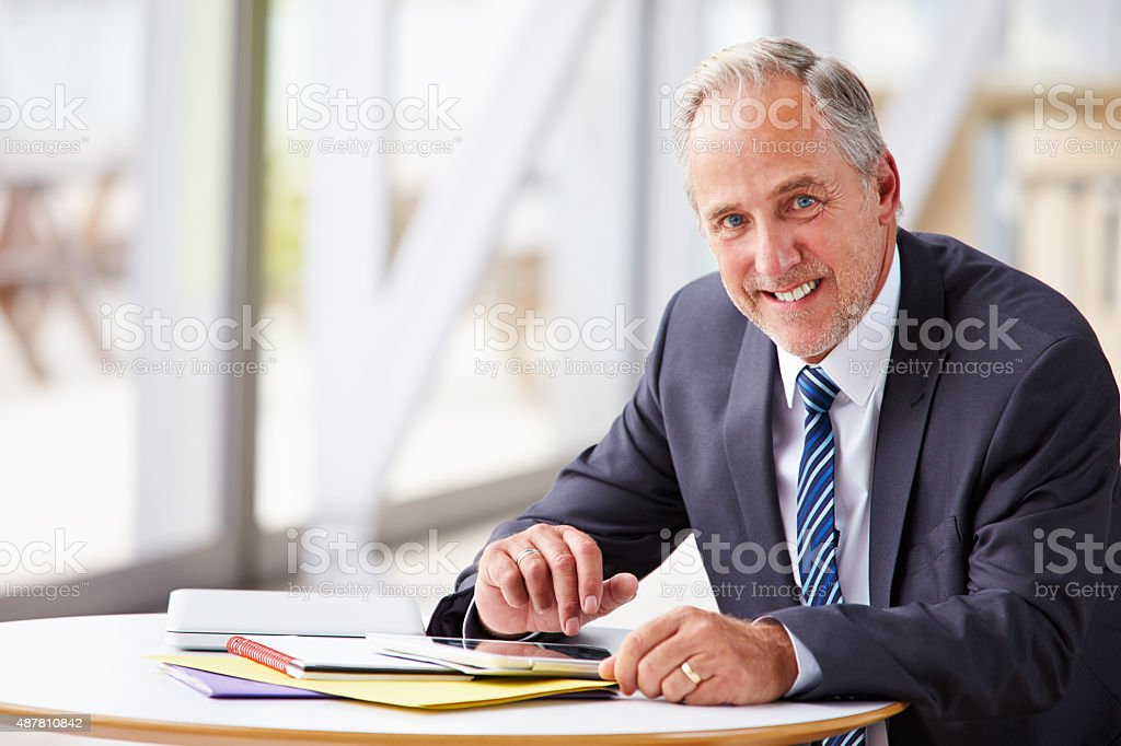 Portrait of smiling senior corporate businessman, waist up stock photo