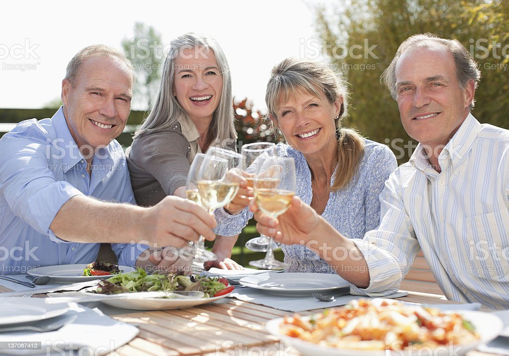 Portrait of smiling senior couples toasting wine glasses at patio table stock photo