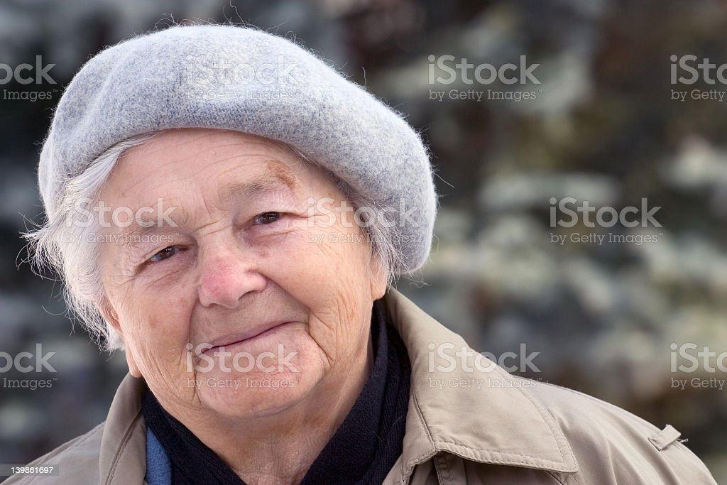 Portrait of smiling senior grey-haired woman in woolen hat stock photo