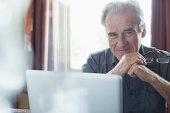 Portrait of smiling senior man holding eyeglasses and using laptop
