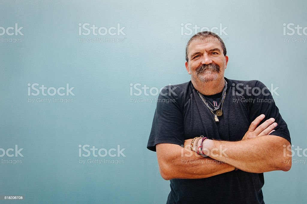 Portrait of smiling senior man with crossed arms stock photo
