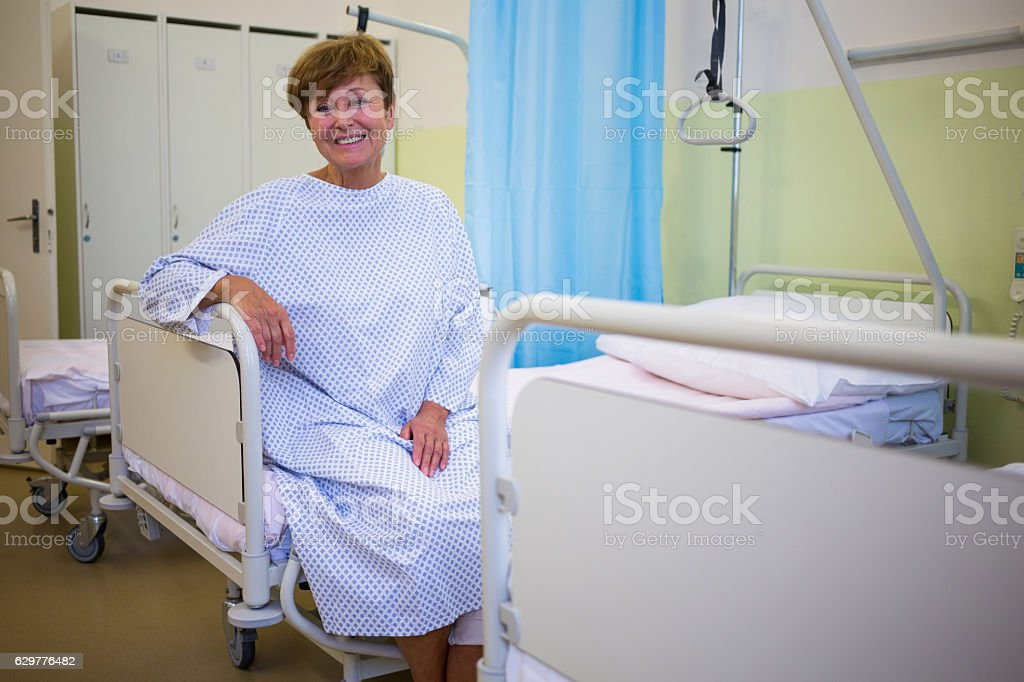 Portrait of smiling senior patient sitting on a bed stock photo