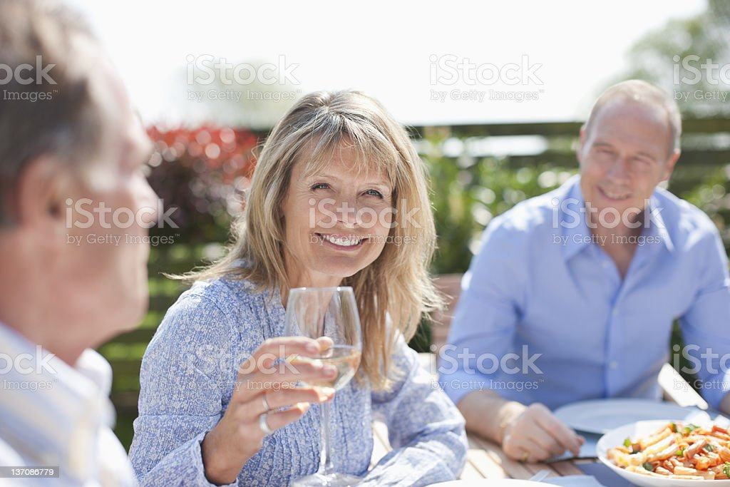 Portrait of smiling senior woman drinking wine at sunny table royalty-free stock photo