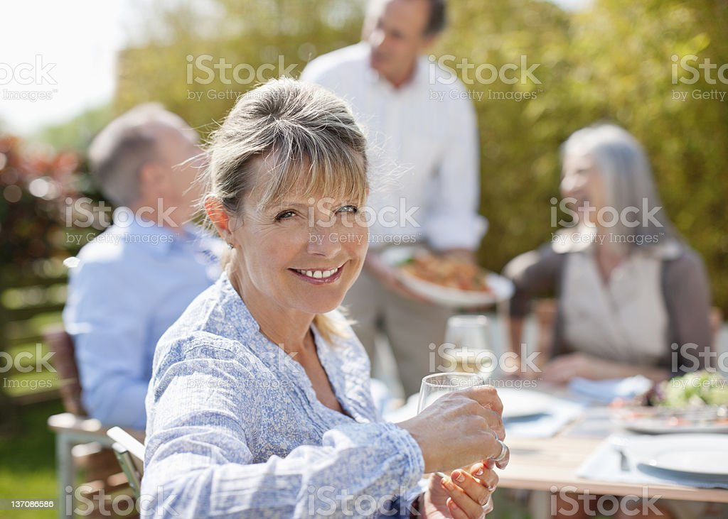 Portrait of smiling senior woman enjoying lunch with friends at sunny table royalty-free stock photo
