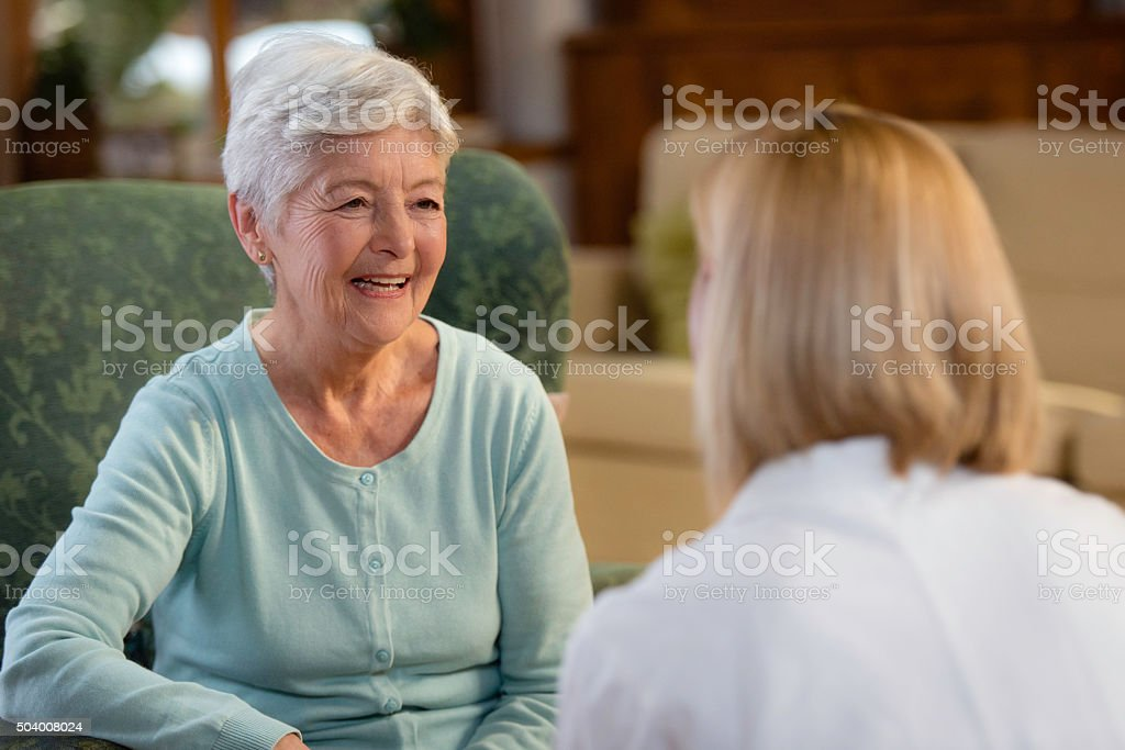 Portrait of smiling senior woman talking with female doctor stock photo