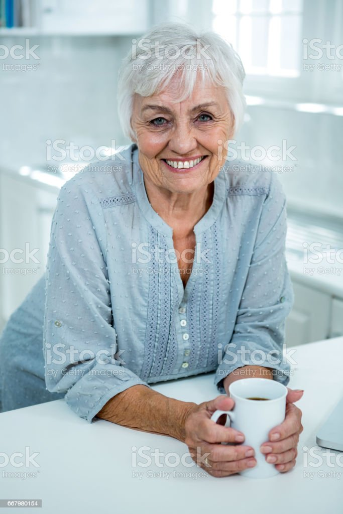 Portrait of smiling senior woman with coffee mug royalty-free stock photo