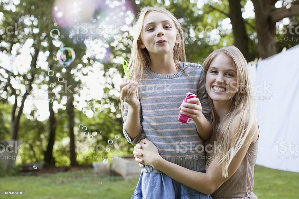 Portrait of smiling sisters blowing bubbles in backyard stock photo