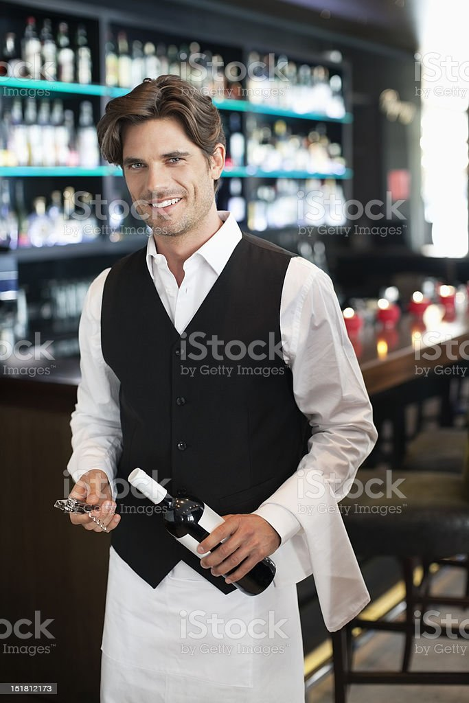 Portrait of smiling sommelier holding bottle of wine in bar royalty-free stock photo