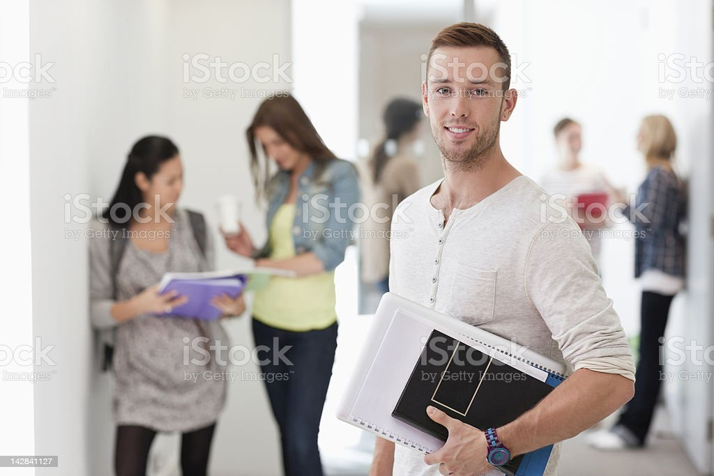 Portrait of smiling university student with books in corridor royalty-free stock photo