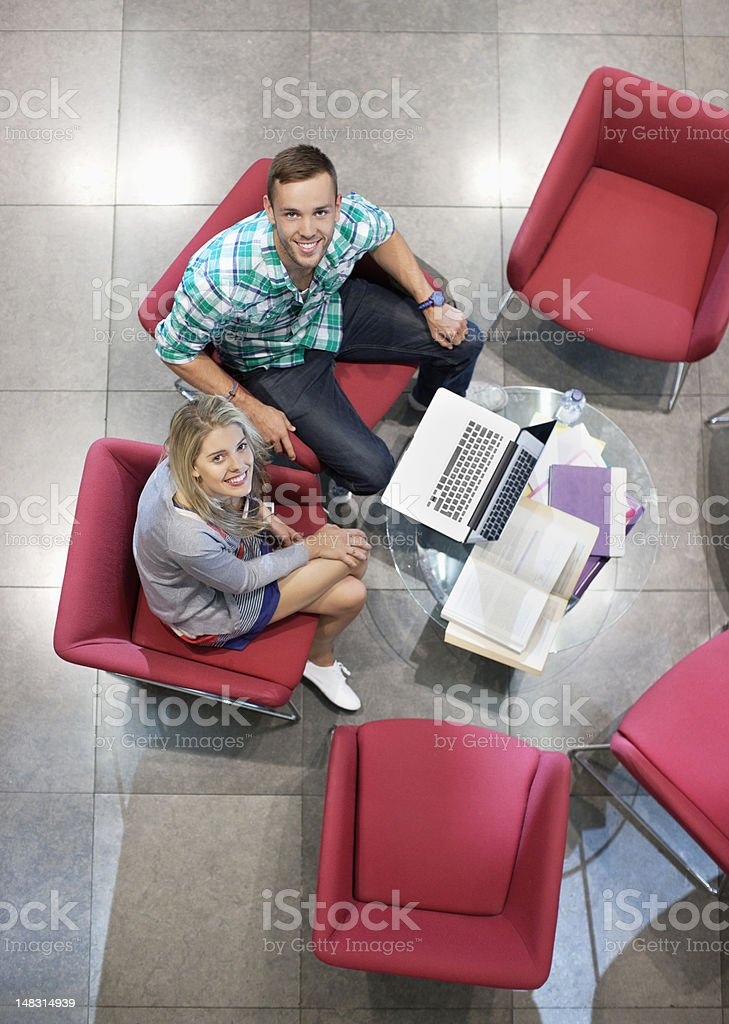 Portrait of smiling university students studying in lounge royalty-free stock photo