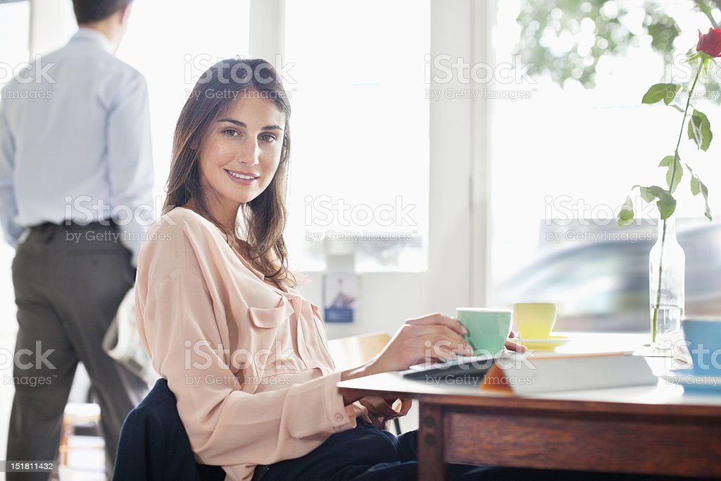 Portrait of smiling woman drinking coffee in cafe stock photo