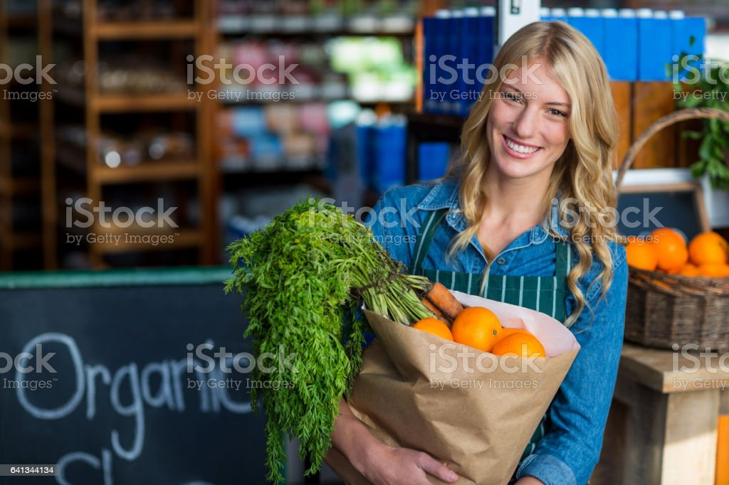 Portrait of smiling woman holding a grocery bag in organic section of supermarket stock photo
