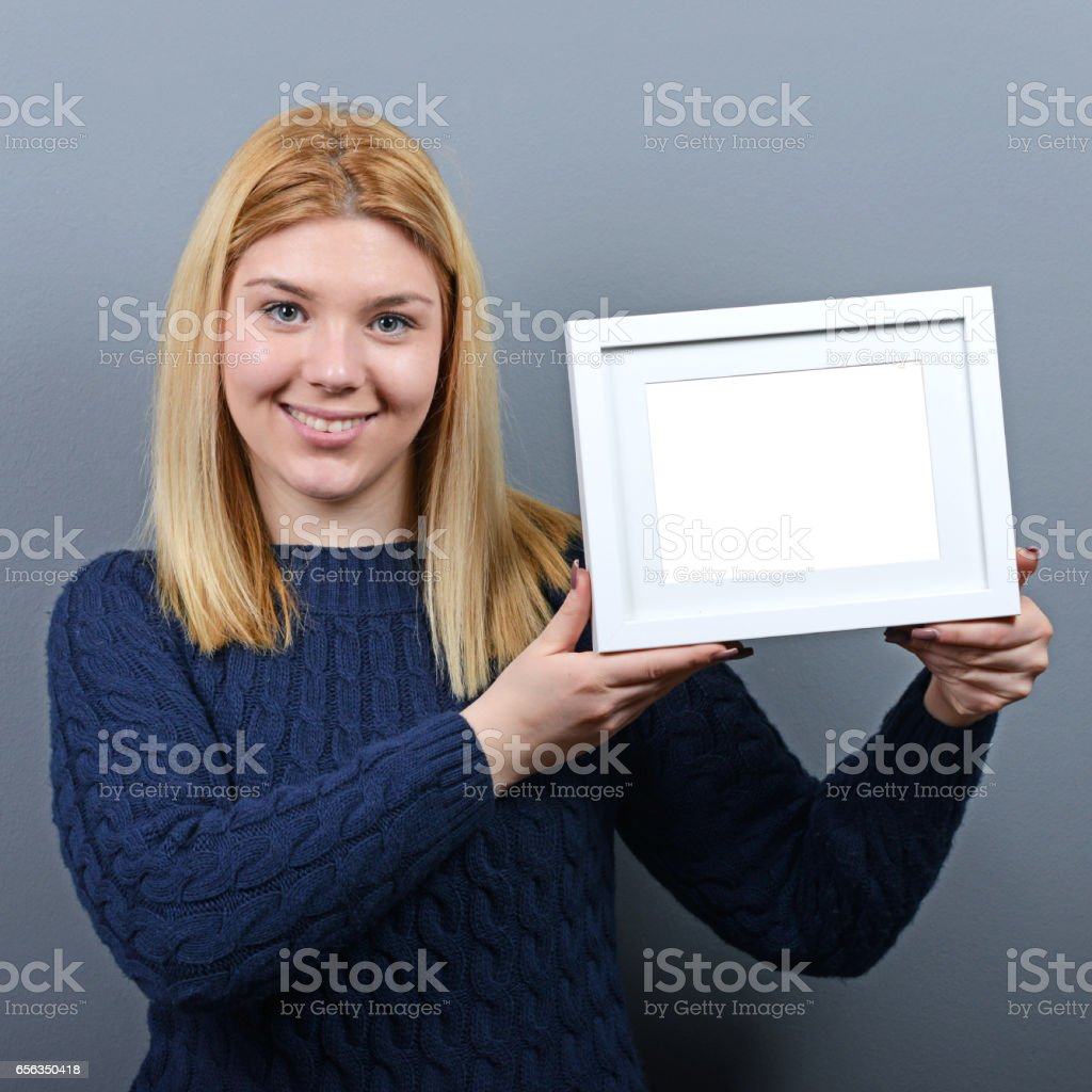 Portrait of smiling woman holding blank photo frame against gray background stock photo