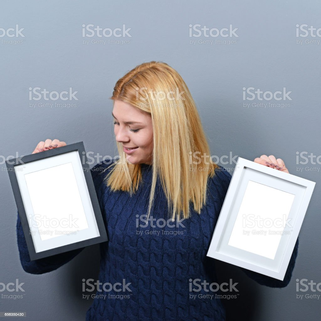 Portrait of smiling woman holding blank photo frames against gray background stock photo