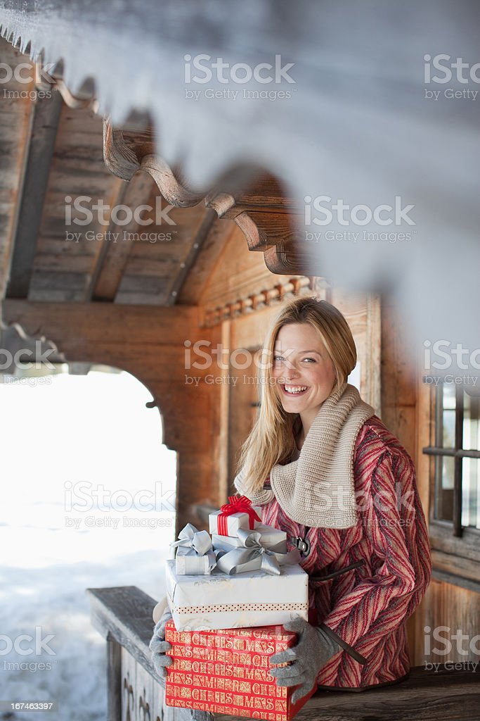 Portrait of smiling woman holding Christmas gifts on cabin porch stock photo
