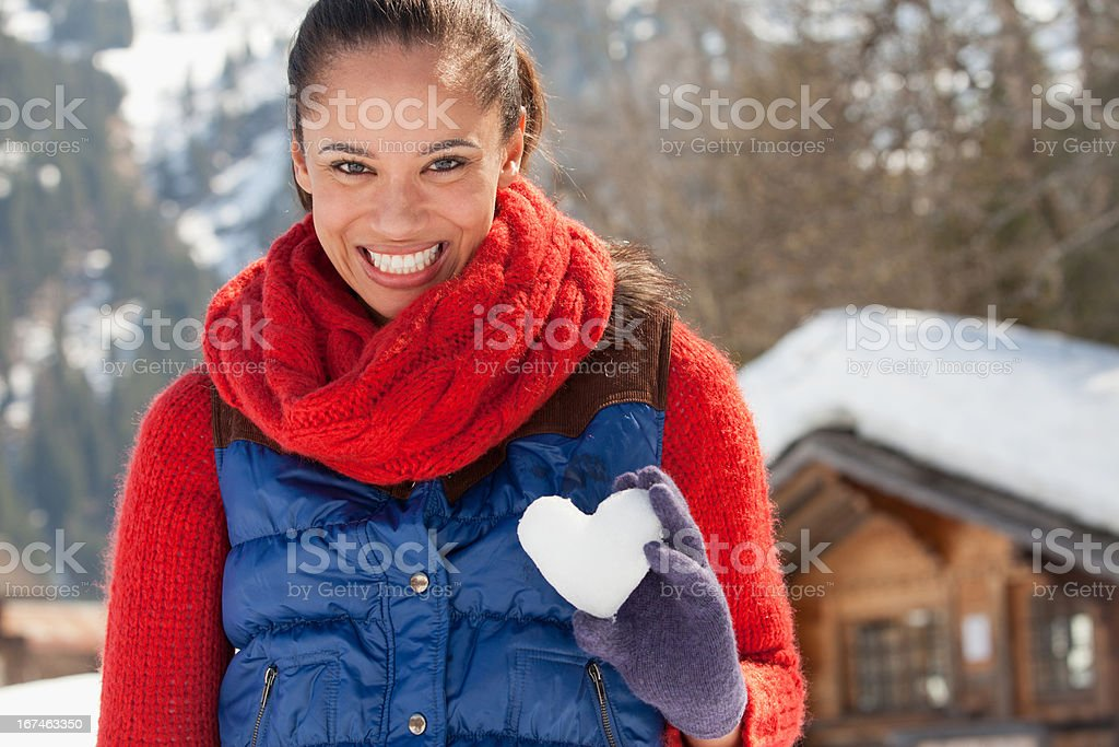 Portrait of smiling woman holding heart-shape snowball royalty-free stock photo