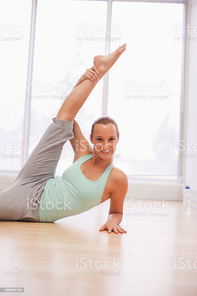 Portrait of smiling woman holding leg overhead in gymnasium royalty-free stock photo