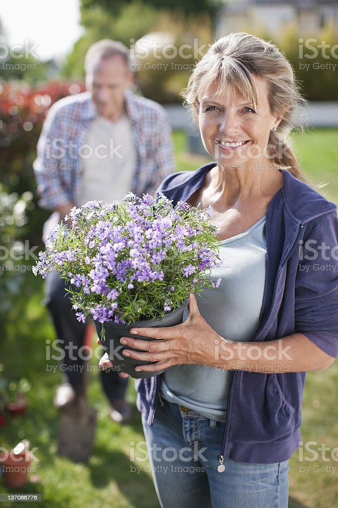 Portrait of smiling woman holding potted flower in garden stock photo