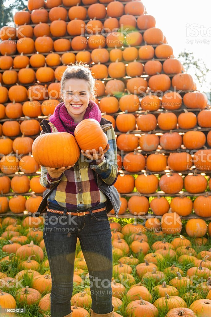Portrait of smiling woman holding pumpkins in autumn outdoors stock photo