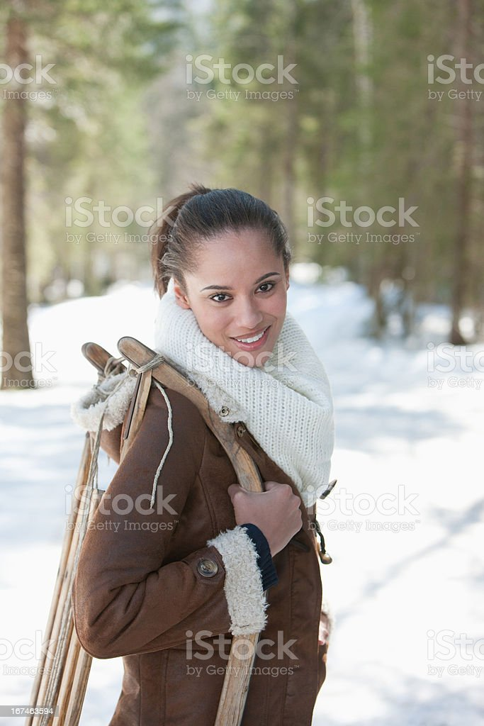 Portrait of smiling woman holding sled in snowy woods stock photo
