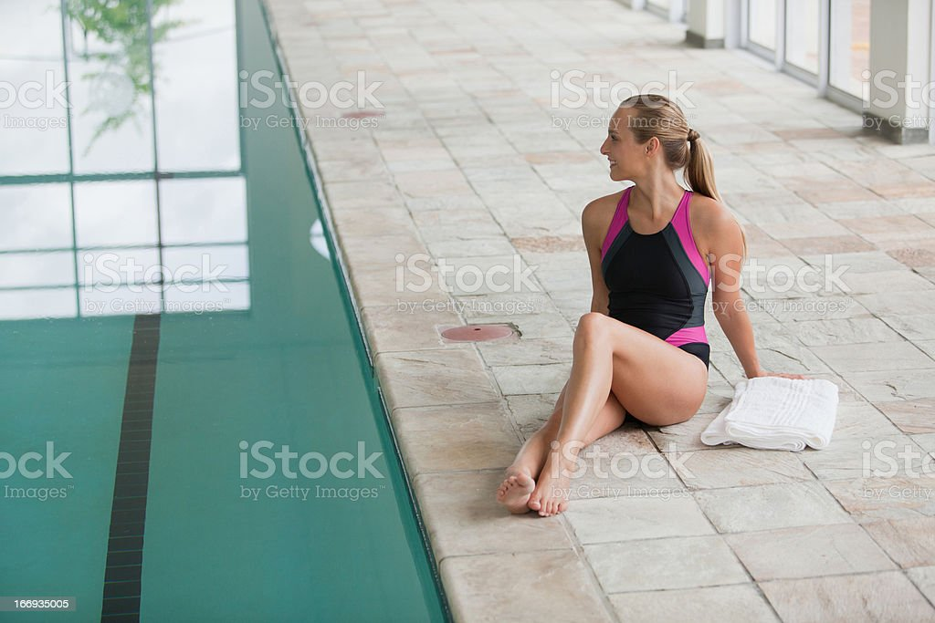 Portrait of smiling woman in bathing suit sitting poolside royalty-free stock photo
