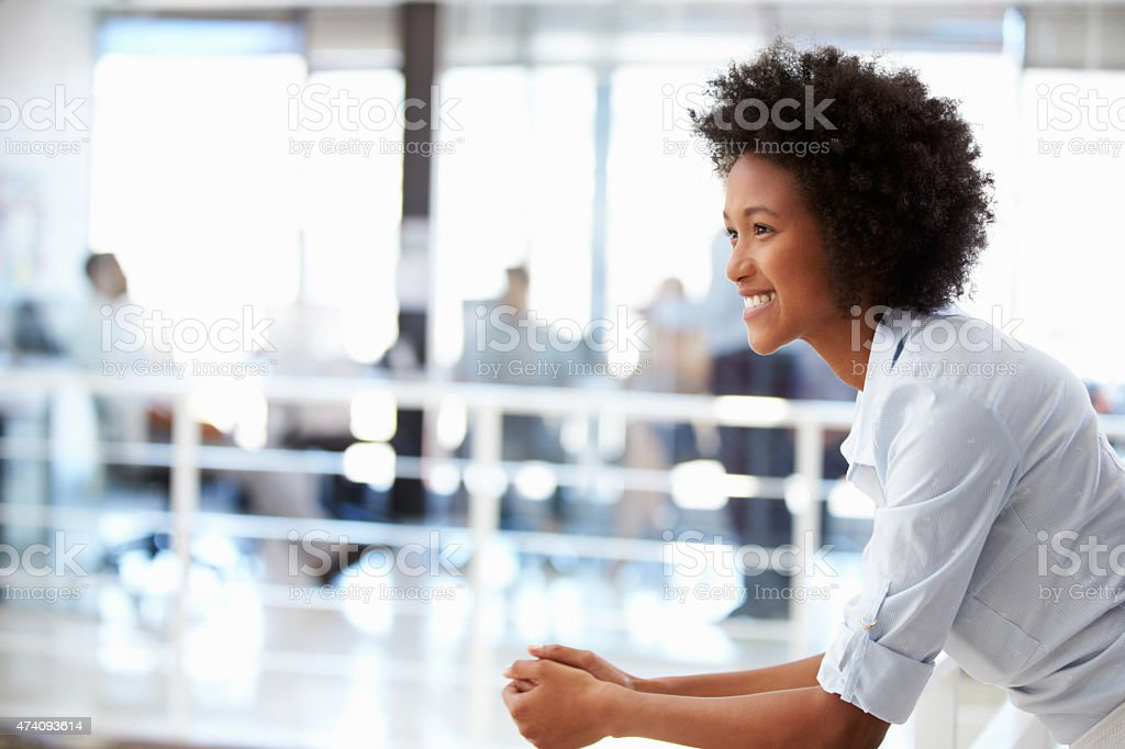 Portrait of smiling woman in office, side view stock photo