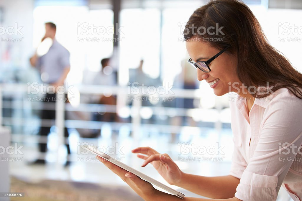 Portrait of smiling woman in office with tablet, side view stock photo