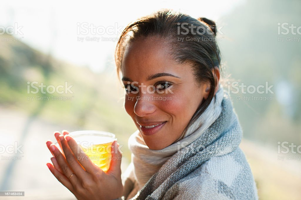 Portrait of smiling woman in scarf drinking cider stock photo