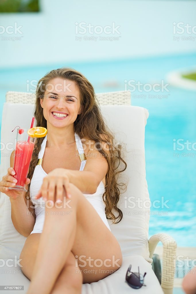 Portrait of smiling woman laying on sunbed and enjoying cocktail royalty-free stock photo