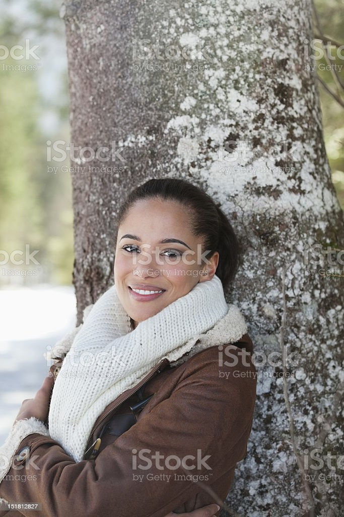 Portrait of smiling woman leaning against tree trunk royalty-free stock photo