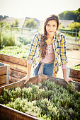 Portrait of smiling woman leaning on crate at community garden