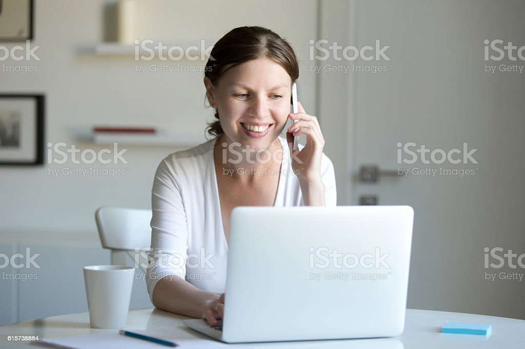 Portrait of smiling woman near laptop talking on the phone. stock photo
