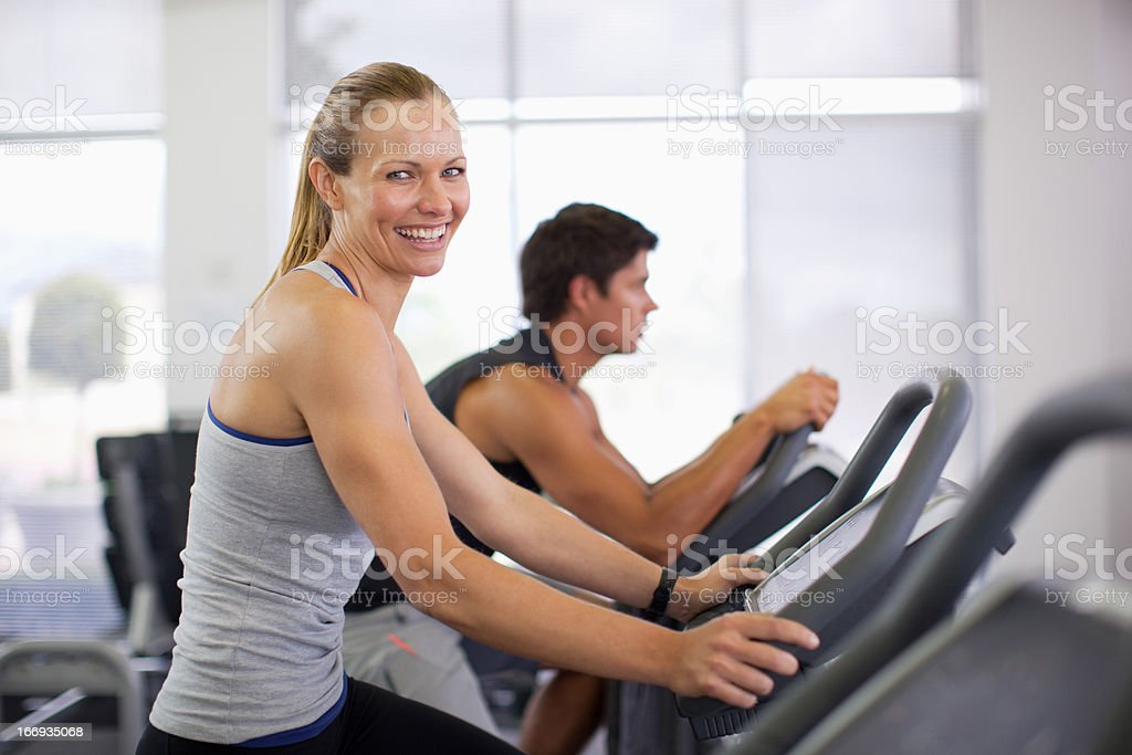 Portrait of smiling woman on exercise machine in gymnasium stock photo