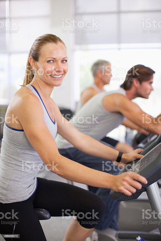 Portrait of smiling woman on exercise machine in gymnasium royalty-free stock photo