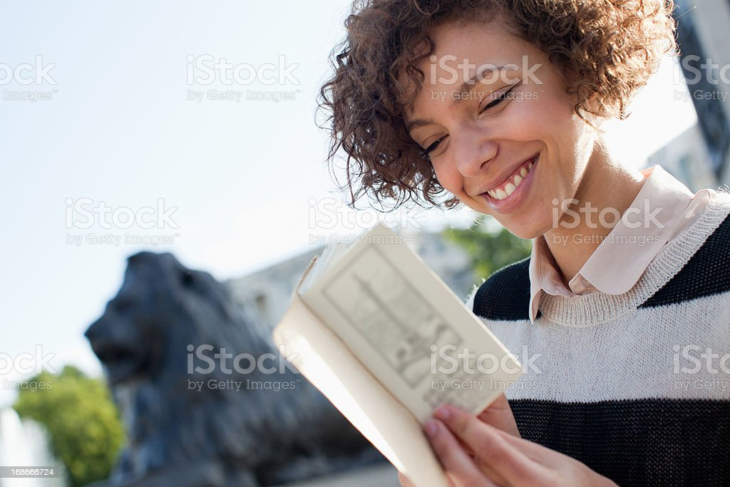 Portrait of smiling woman reading book royalty-free stock photo