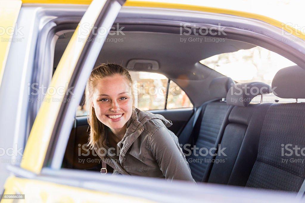 Portrait of smiling woman seen through car door stock photo