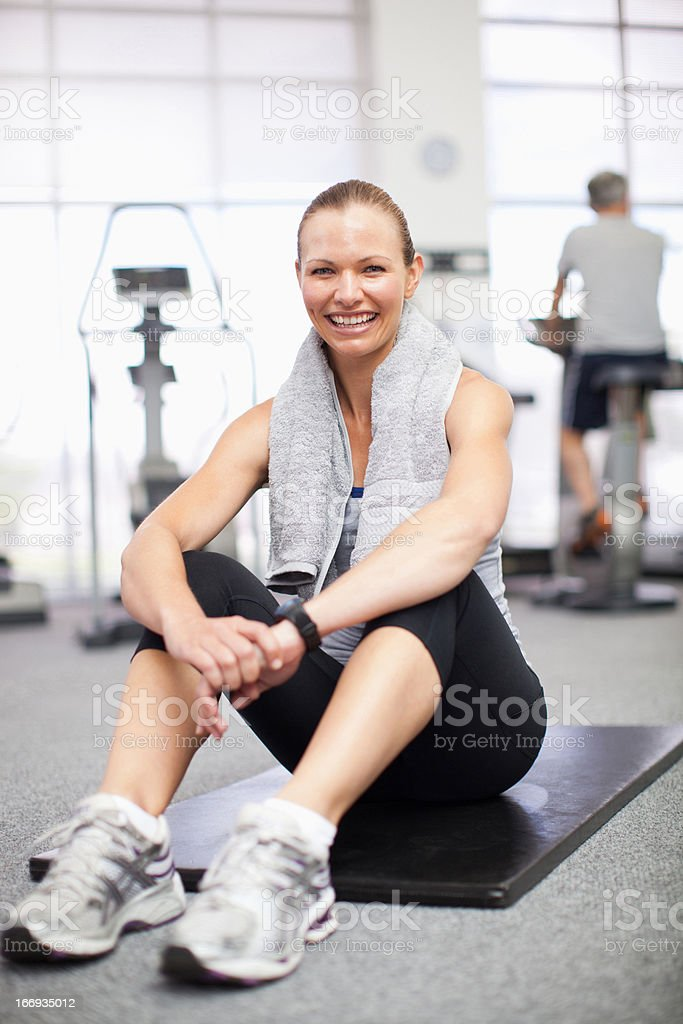 Portrait of smiling woman sitting on exercise mat in gymnasium royalty-free stock photo