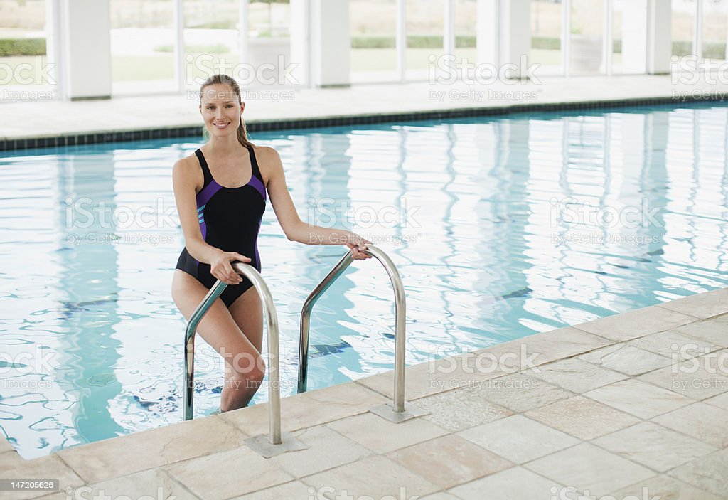 Portrait of smiling woman standing on ladder in swimming pool stock photo
