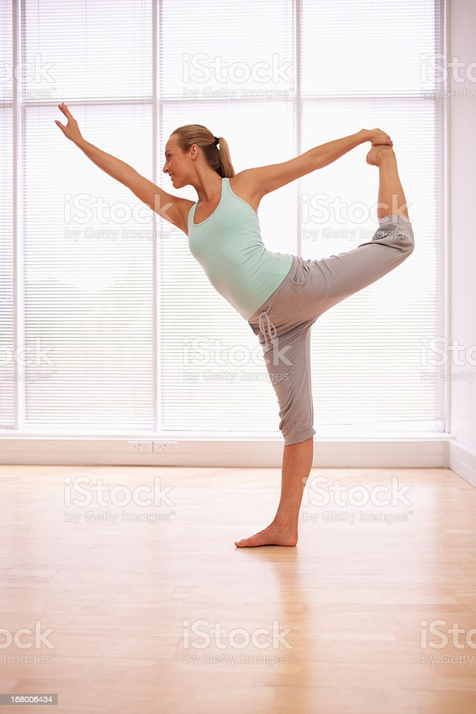Portrait of smiling woman stretching in fitness studio royalty-free stock photo