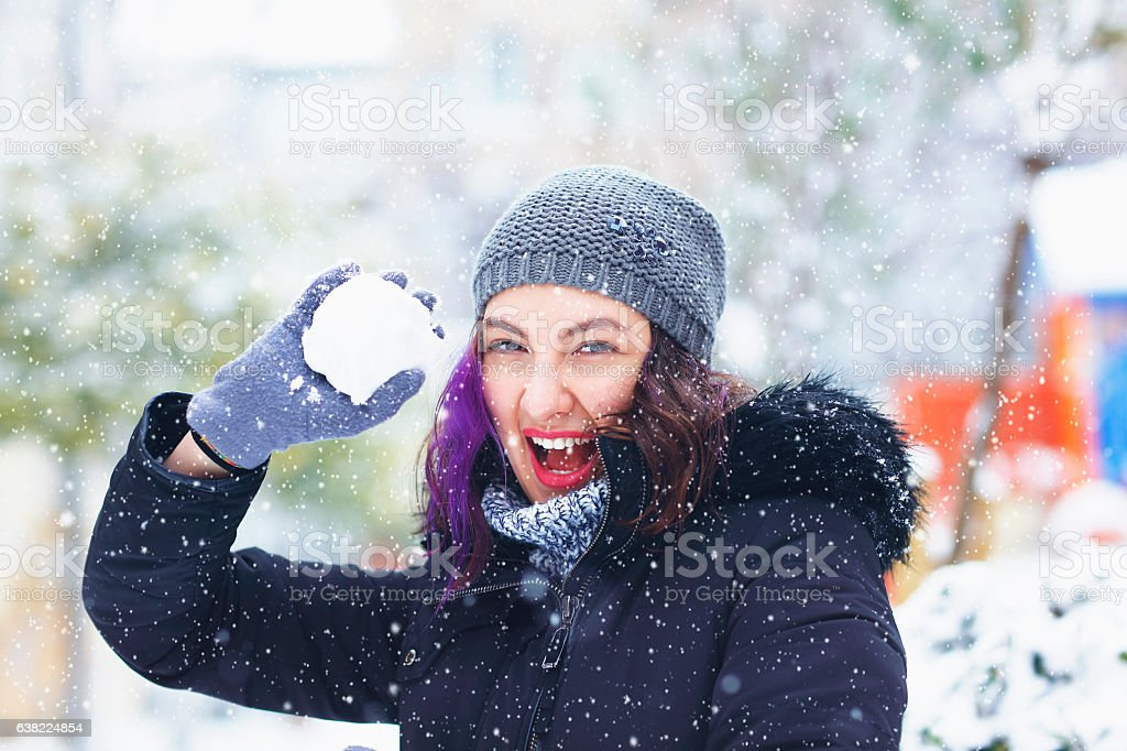 Portrait of smiling woman throwing snowball stock photo