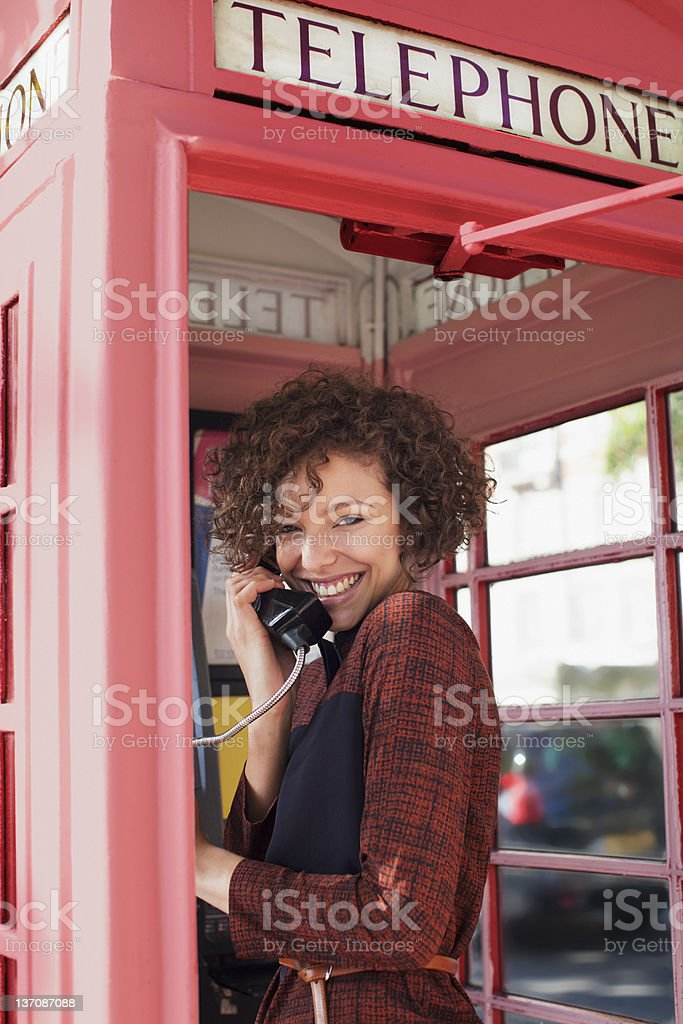 Portrait of smiling woman using telephone booth royalty-free stock photo